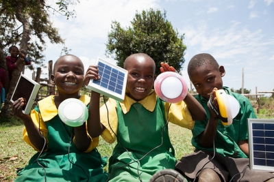 Primary school students holding solar lights in Kenya.